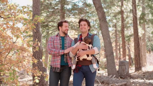 vídeos de stock, filmes e b-roll de masculino pais na floresta com bebê no sling passe de foto - homossexualidade