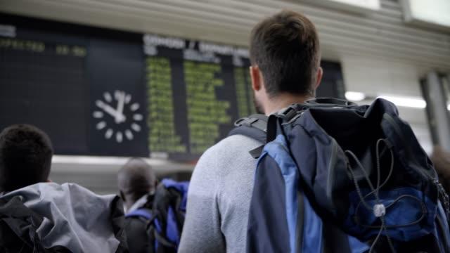 male passenger looking at the flight information display at the airport - табло вылетов и прилётов стоковые видео и кадры b-roll