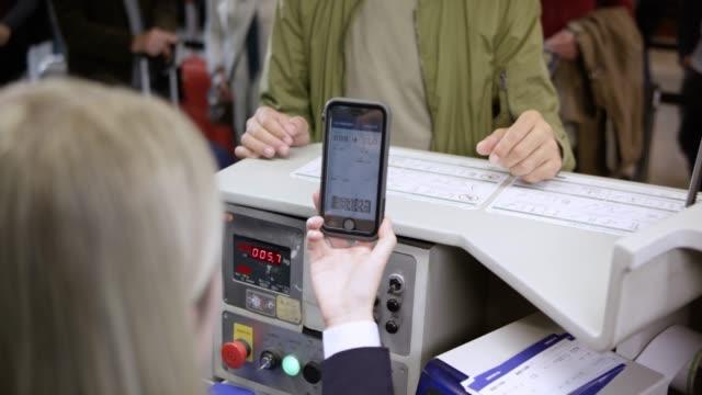 stockvideo's en b-roll-footage met mannelijke passagiers bagage op de transportband brengen en instapkaart waarop de smartphone - vliegveld vertrekhal