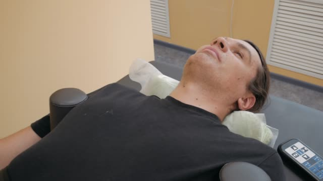 Male patient at non-surgical spinal decompression procedure for stretching spine in medical center on special modern medicine equipment video