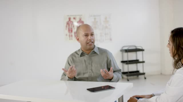 Male Patient Seeks Advice from Medical Professional in Consultation A balding male patient seeks advice from his female doctor while in consultation appointment nutritionist stock videos & royalty-free footage