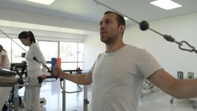 manlig patient tränar sina armar och bröst under fysisk rehab medan kvinnliga patienter tränar på olika maskiner - axel led bildbanksvideor och videomaterial från bakom kulisserna