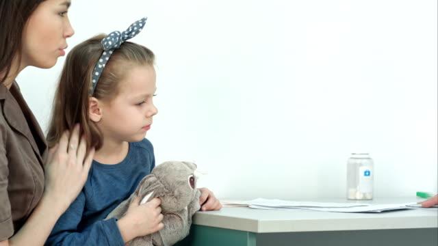 Male pediatrician checking little girl head for fever video