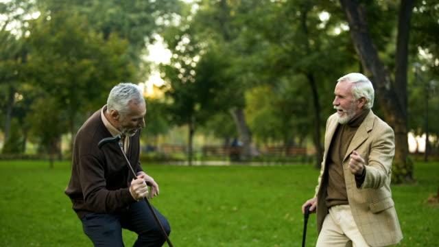 erkek emekliler parkı dostluk mizah, baston ile dans eğleniyor - nükteli stok videoları ve detay görüntü çekimi