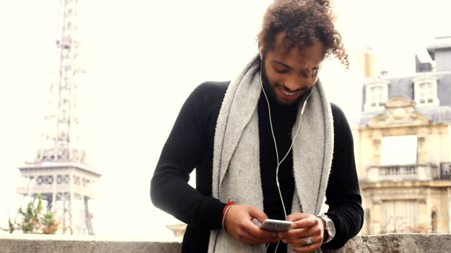 Mulatto male person chatting with friends by smartphone with earphones near Eiffel tower video