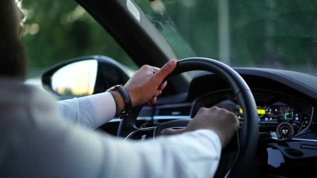 Male person driving car in evening time, modern vehicle interior Experienced male driver holding hands on wheel in interior of car respecting road security and speed limits while moving in city. Slow motion of businessman in white shirt steering luxury automobile button down shirt stock videos & royalty-free footage