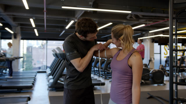 male personal coach measuring arms and waist of young woman who has been training at the gym - chudy filmów i materiałów b-roll