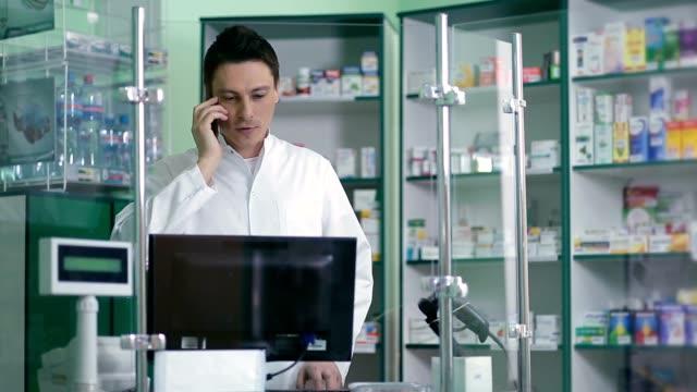 Male pharmacist communicating on phone in pharmacy video