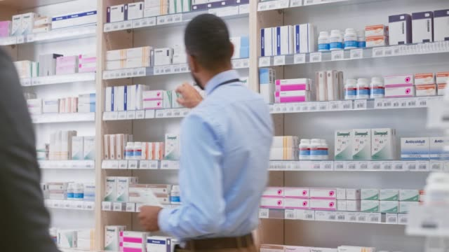 male pharmacist picking the medicine from the shelf and handing it to the male customer - integratore vitaminico video stock e b–roll