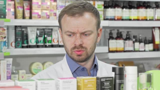 männlicher apotheker, der in seiner drogerie arbeitet und lager in einem gang überprüft - kosmetik beratung stock-videos und b-roll-filmmaterial