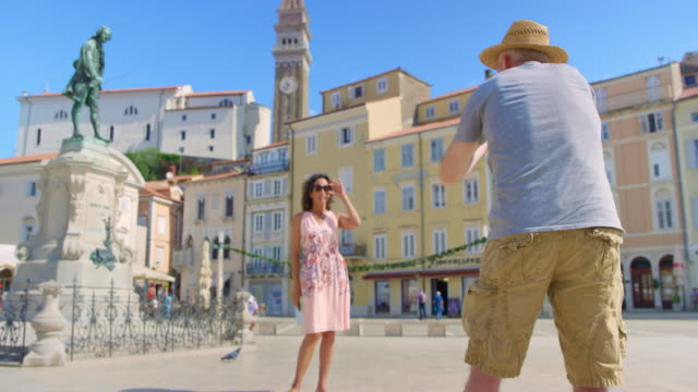 Male photographer directing a female model while taking photos in the square of a coastal town