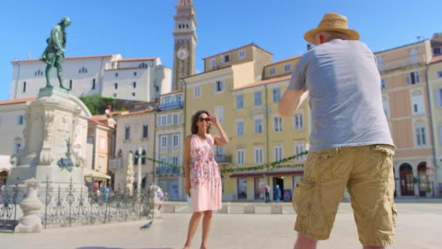 男性カメラマンの海岸沿い町の広場で写真を取っている間女性モデルを演出 - スロベニア点の映像素材/bロール