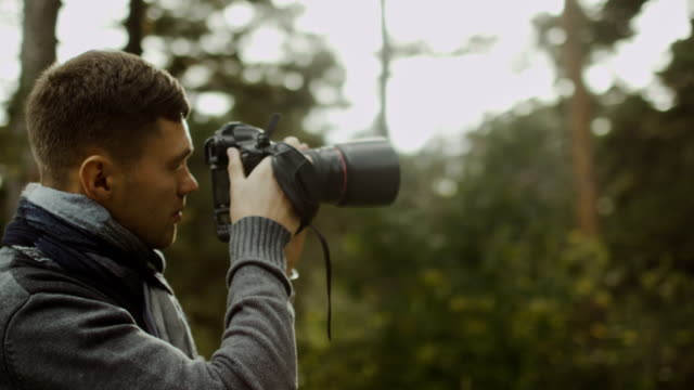 Male photographer is taking photographs in a forest at autumn time. video
