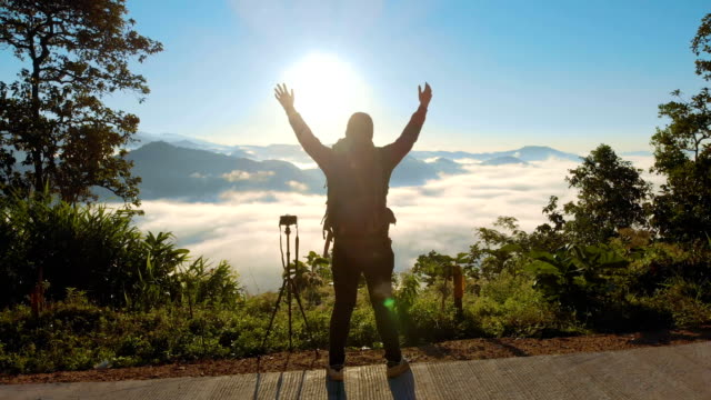 AERIAL Male Photographer standing on the mountain and raising his hands in morning sunrise