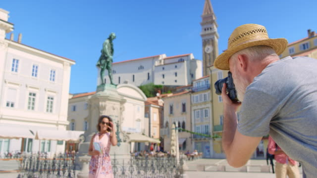 Male photographer taking a photo of a woman in a town square on a sunny day