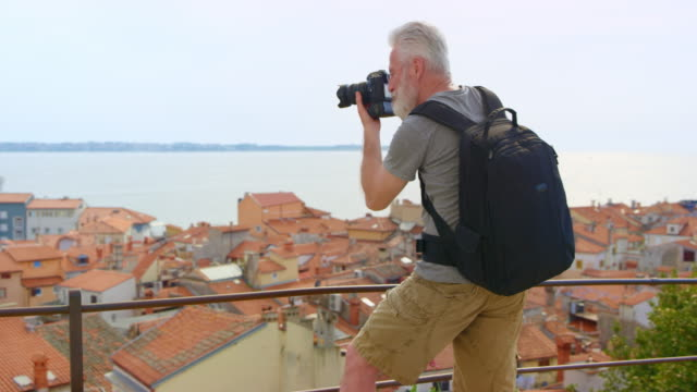 male photographer with grey hair and beard taking photos of the picturesque coastal town below him - 50 54 lata filmów i materiałów b-roll