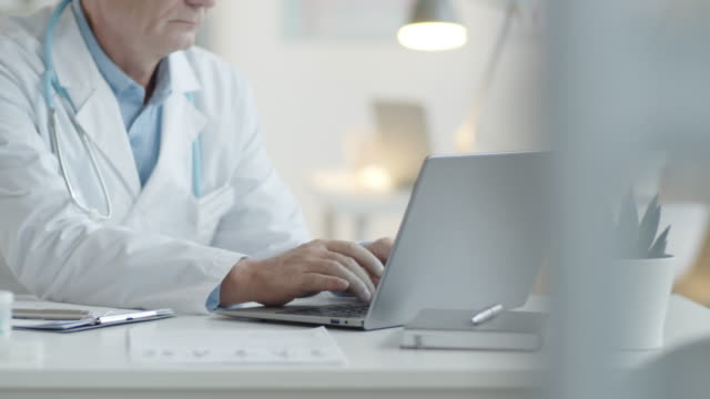 Male Physician Typing on Laptop at Desk in Clinic
