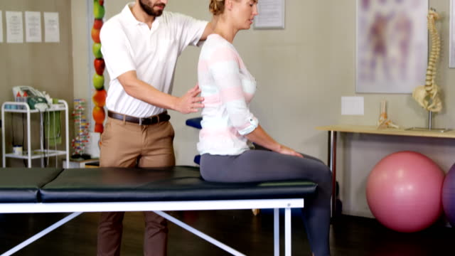 Male physiotherapist giving back massage to female patient video