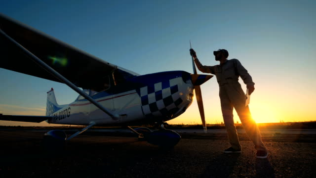 Male pilot wipes a plane's propeller, side view.