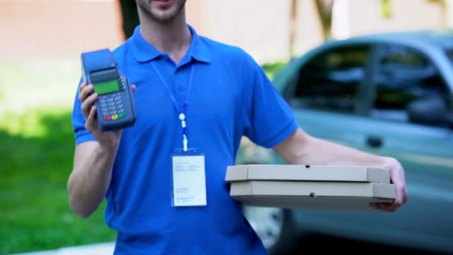 Male pizza courier holding credit card terminal, payment technology, service