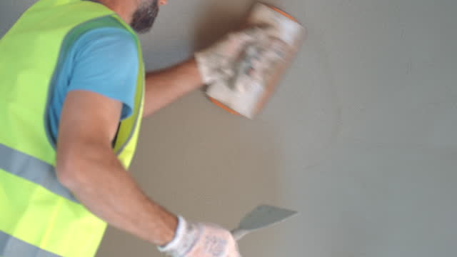 Male plasterer evening the plaster layer for a smooth finish