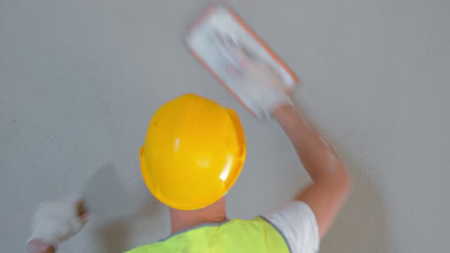 Male plasterer smoothening out a plaster layer