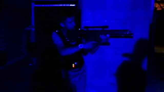 männliche spieler verstecken sich vor rivalen mit lasertag pistole, genießen sie realistische kampfspiel - etikett stock-videos und b-roll-filmmaterial