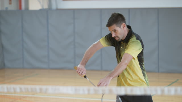 Male player playing indoor badminton video