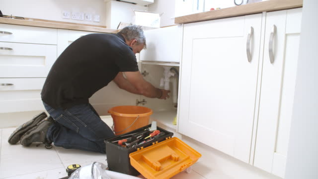 Male plumber preparing a pipe for the sink in a kitchen video