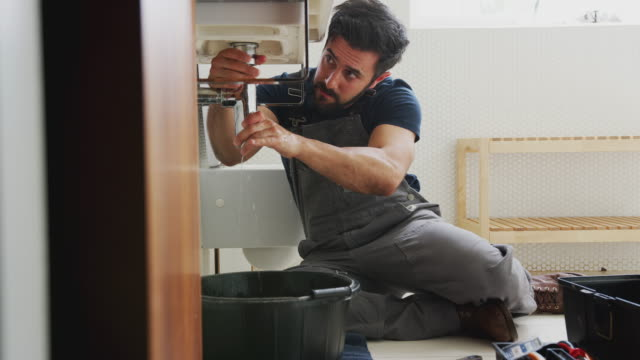 Male Plumber Working To Fix Leaking Sink In Home Bathroom Camera tracks across frame as male plumber fixes leaky pipe on bathroom sink - shot in slow motion water pipe stock videos & royalty-free footage