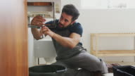 istock Male Plumber Working To Fix Leaking Sink In Home Bathroom 1185630079