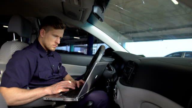 Male police officer working on laptop in car, filling data in crime report Male police officer working on laptop in car, filling data in crime report military uniform stock videos & royalty-free footage
