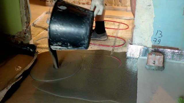 male pouring concrete on heating cable for installing comfortable and adjustable warm floor