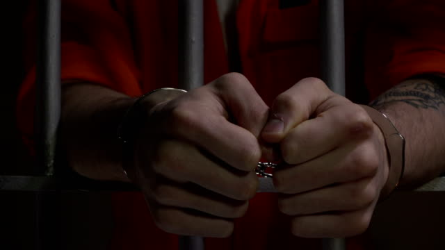 4k dolly: male prisoner in jail cell handcuffed - арест стоковые видео и кадры b-roll
