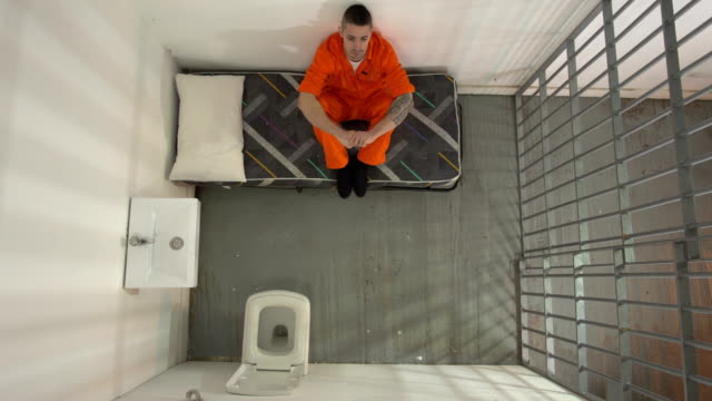 4K AERIAL: Male Prisoner in Jail Cell Sat on bed Stock 4K video clip footage of a male prisoner in a Jail / Prison Cell. The man is sat on his bed, looking up to the ceiling. He is looking very upset and distressed. The camera is looking down from the ceiling. prison bars stock videos & royalty-free footage