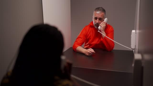 stockvideo's en b-roll-footage met mannelijke gevangene die met zijn vrouw in gevangenis bezoekruimte spreekt - raam bezoek