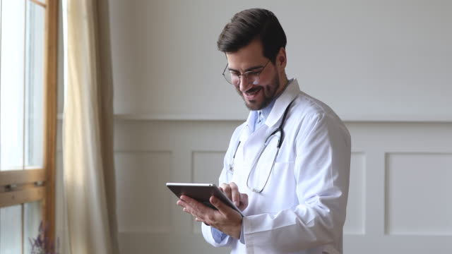Male professional doctor wear white uniform holding using digital tablet Smiling male professional medic doctor surgeon wear white uniform stethoscope holding using digital tablet computer check medical data stand alone in hospital office, healthcare technology concept general view stock videos & royalty-free footage