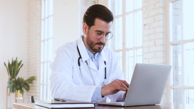 Male professional medic doctor wear medical coat using laptop computer Male professional medic doctor wear medical coat using notebook computer, man general practitioner physician working on laptop technology in hospital check digital data chatting with patient concept cardiologist stock videos & royalty-free footage