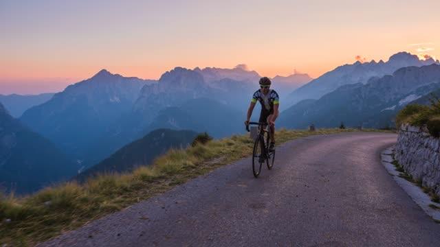 male professional road cyclist cycling uphill - ciclismo su strada video stock e b–roll
