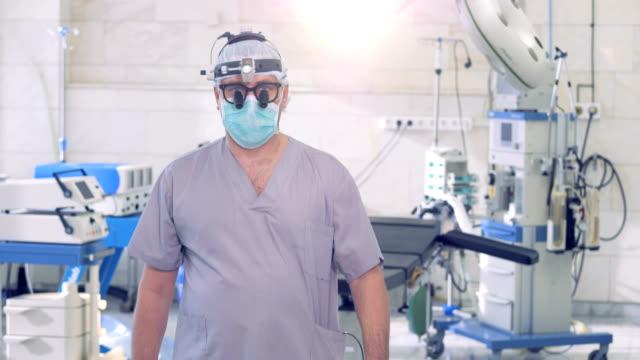 Masculino profissional cirurgião está andando e parando na frente de uma câmera, enquanto olhando diretamente para ele - vídeo
