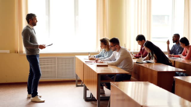 Male professor in casual clothes is talking to group of students sitting at tables in classroom and making notes. Large lecture hall with desks, chairs and windows is visible. video