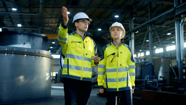 Male Project Manager with Mobile Phone and Female Industrial Engineer Having Discussion While Walking Through Heavy Industry Manufacturing Factory. Big Metalwork Constructions, Pipeline Elements Lying Around. video
