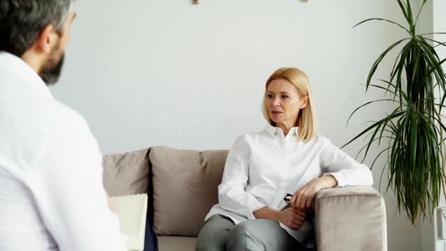 vídeos y material grabado en eventos de stock de paciente femenino adulto escucha hombre psicoanalista con la depresión en la oficina del psicólogo - profesional de salud mental