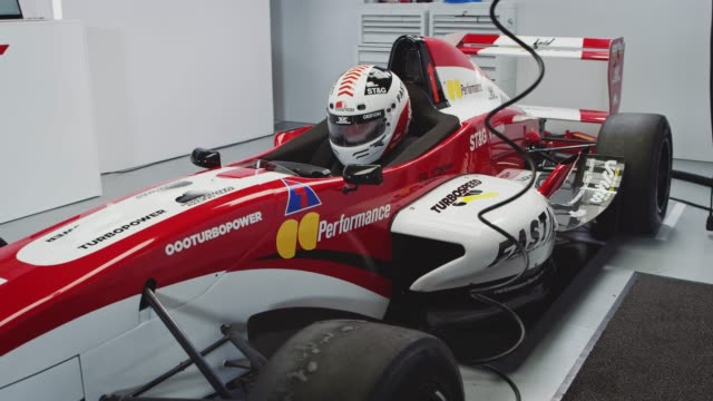 Male racer sitting in red racing car at laboratory Handheld shot of driver sitting in red and white racing car. Motor vehicle with text is in laboratory. He is at pit stop. crash helmet stock videos & royalty-free footage