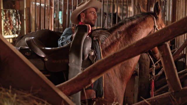 DS Male rancher putting a saddle on his horse video