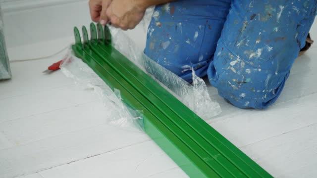 Male repairman unpacks green metal structures from polyethylene video