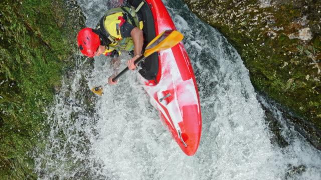 vidéos et rushes de slo mo mâle cavalier exécutant une cascade dans un kayak rouge - kayak