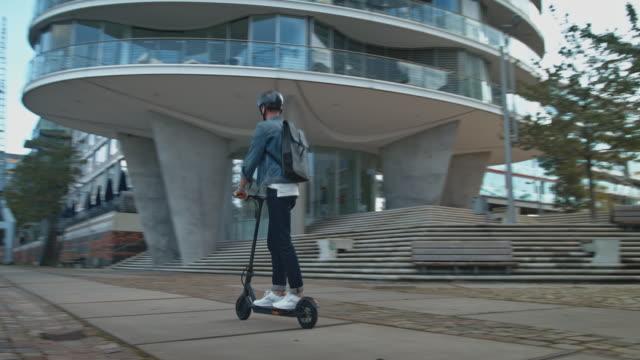 male riding electric kick scooter in city - monopattino elettrico video stock e b–roll