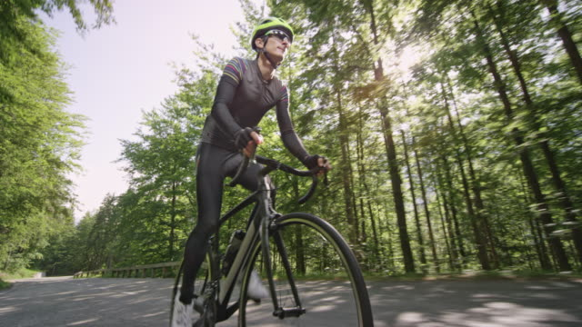 ts male road cyclist cycling up a nice mountain road in sunshine - ciclismo su strada video stock e b–roll