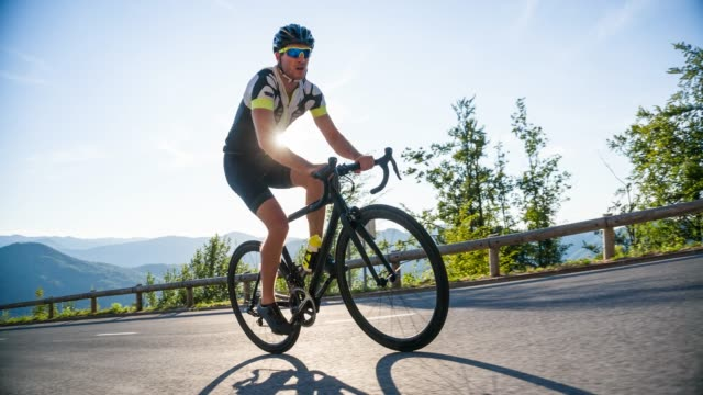 male road cyclist cycling uphill, going into a turn on a winding road - ciclismo su strada video stock e b–roll
